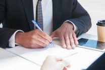 Closeup of business man writing on paper sheet at table. Business man and partner sitting at desk with tablet and coffee outdoors. Paperwork concept. Cropped view.